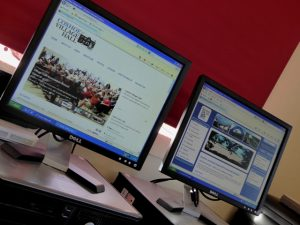 Photograph of two computer screens, one with the Parish council website on and one with the Village Hall website