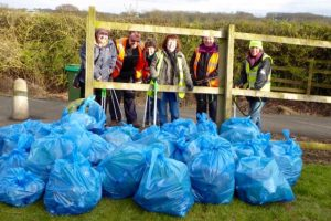 Photograph of volunteer litter pickers with bags of rubbish. Litter pickers are on Parsons Walk
