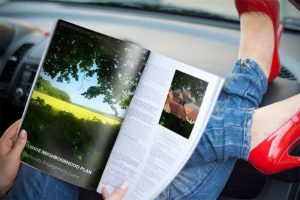 Photograph of promotional material featuring picture of lady looking at neighbourhood planning magazine.