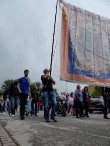 Photograph of people marching the banner