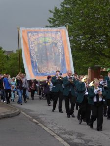Photograph of marching band with banner in Petterson Dale