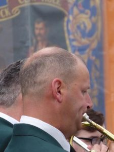 Photograph of trumpeteer with receeding hair and banner behindwith banner floating in the background