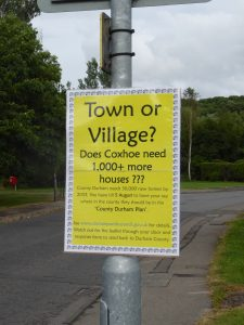 Photograph of sign publicising impact of 1000 houses in Coxhoe during survey.