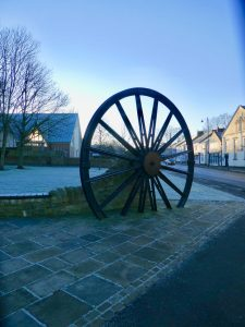 Photograph of pit wheel on a frosty day looking south in low light. Wheel is like a silouette