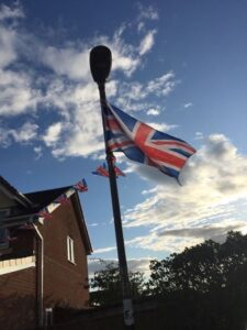 Flag flying with bright sunlight behind