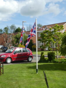 two flags on masts in a garden