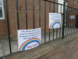 Two rainbow notices on church fence