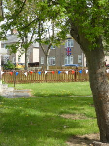 A streetcene with visible bunting and flags