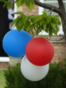 a red white and a blue balllon hanging